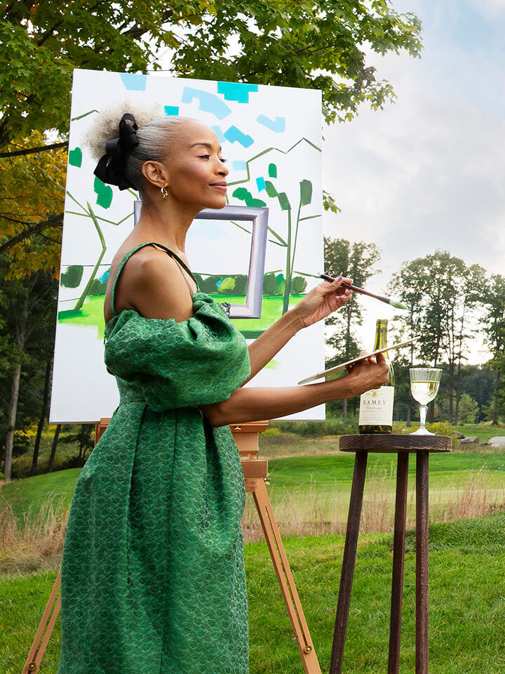 A lady in a green dress painting outside.