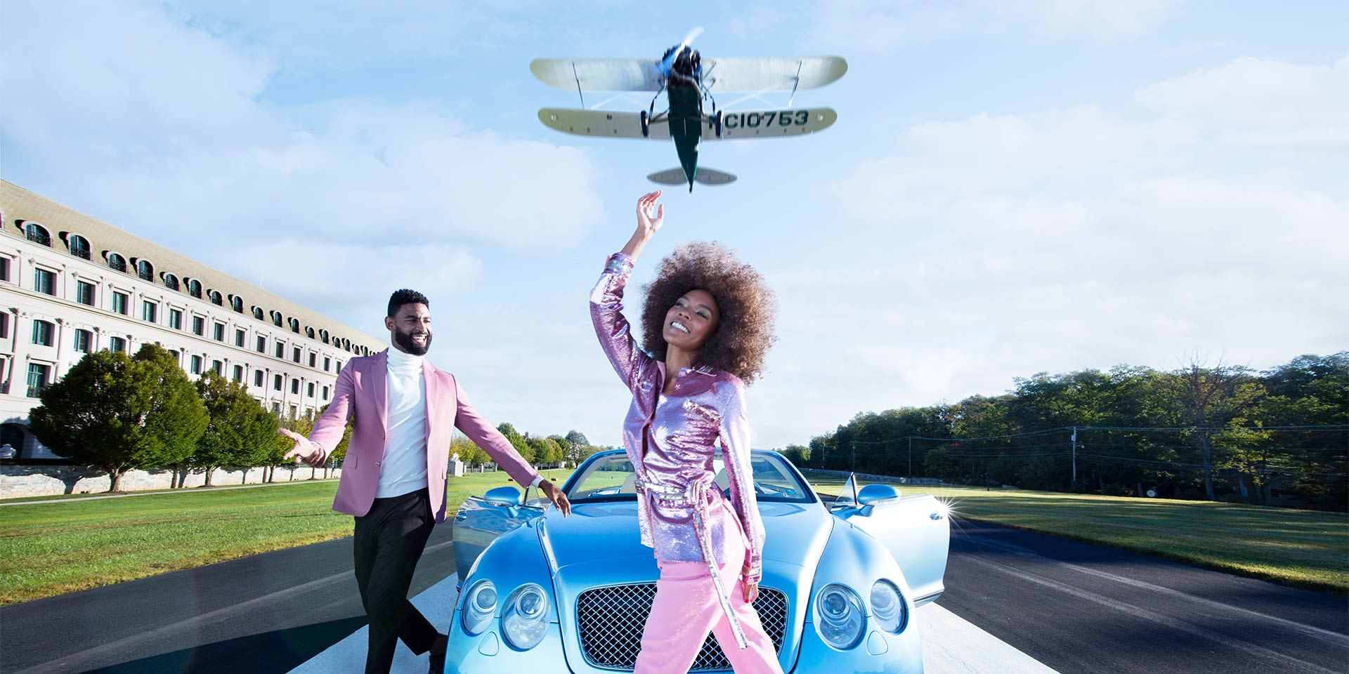 A couple dressed in pink attire walking near a blue car with a airplane flying above them.