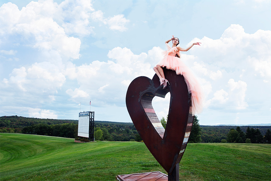woman on a heart shaped sculpture in a green field
