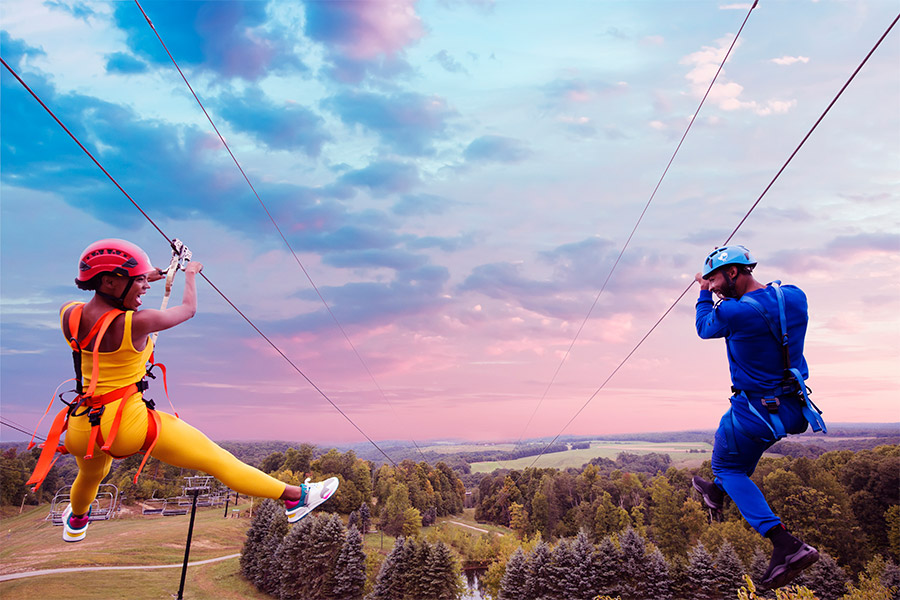 Couple zip-lines over a sunset