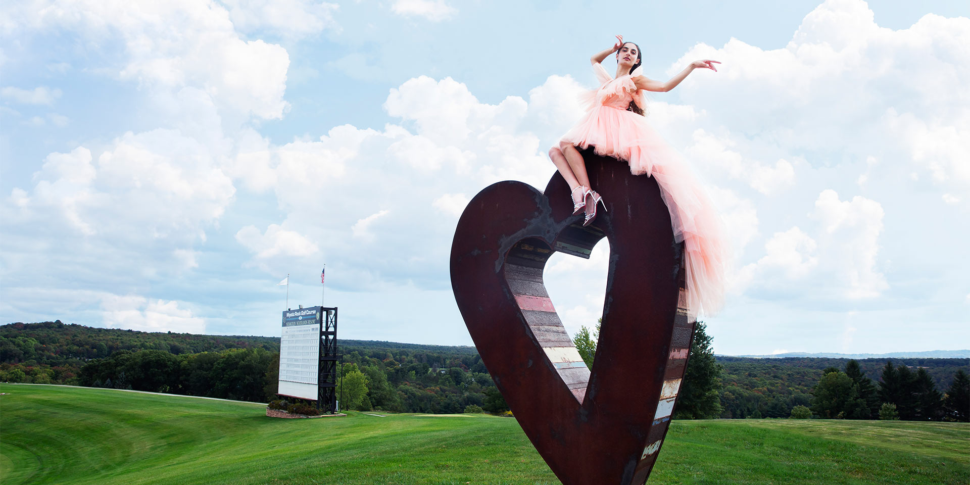 Woman on a heart statue in a a field